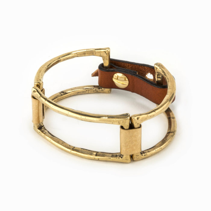 A brass cuff with large square pieces linked together with 14k gold fill plates and an adjustable leather closure.