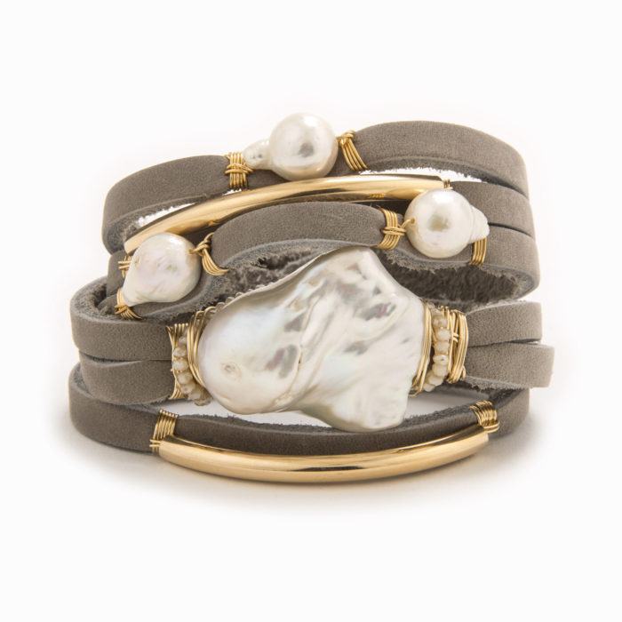 A taupe-colored leather wrap bracelet with wire wrapped in 14k gold fill tubes with baroque and fresh water pearl.