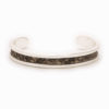 A small silver cuff with grey and brown colored snake pattern inlay.A small silver cuff with grey and brown colored snake pattern inlay.