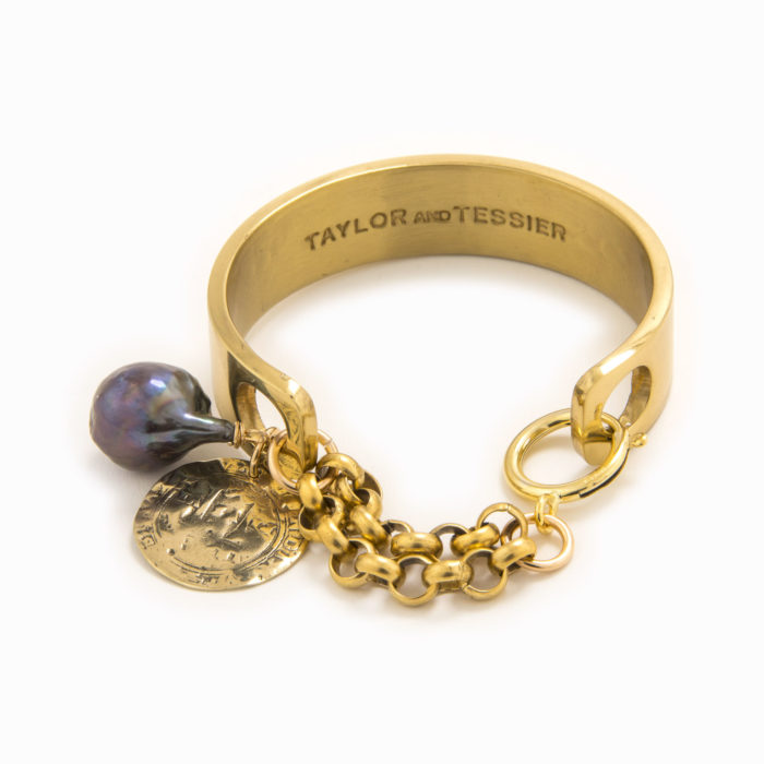 Front view of an adjustable handcuff in solid brass with a gold coin, black freshwater pearl and lobster claw closure.