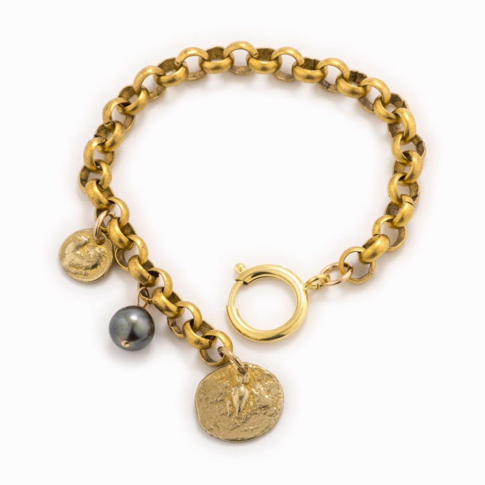 An adjustable brass rolo chain bracelet with a stamped coin charm and tahitian pearl.