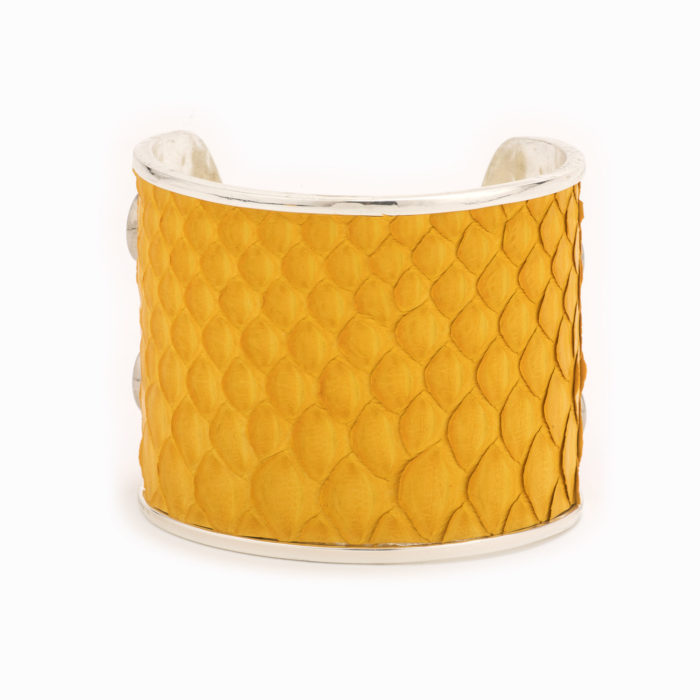 A large silver cuff with mustard colored snakskin pattern inlaid.