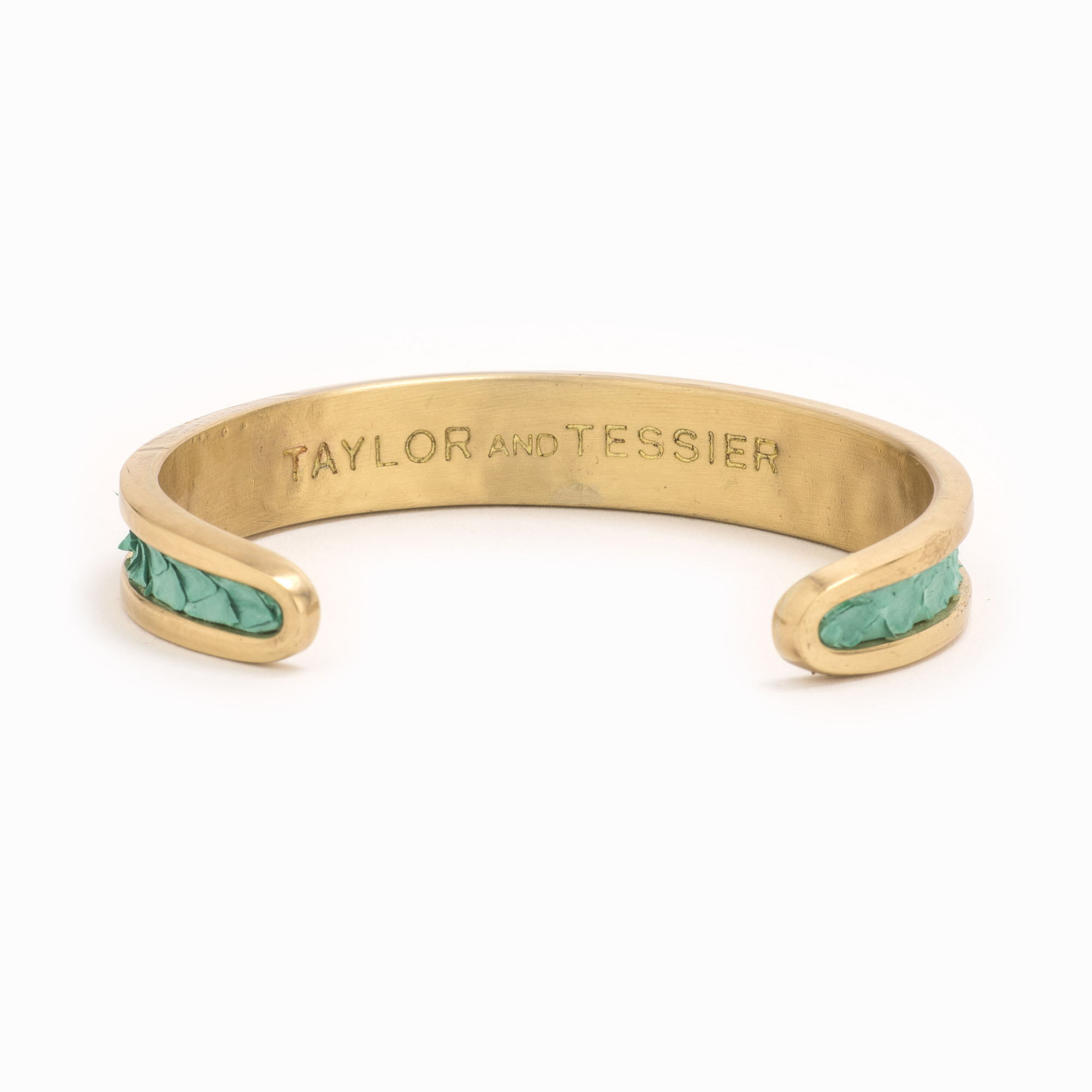 A small gold cuff with turquoise colored snakeskin pattern inlaid.