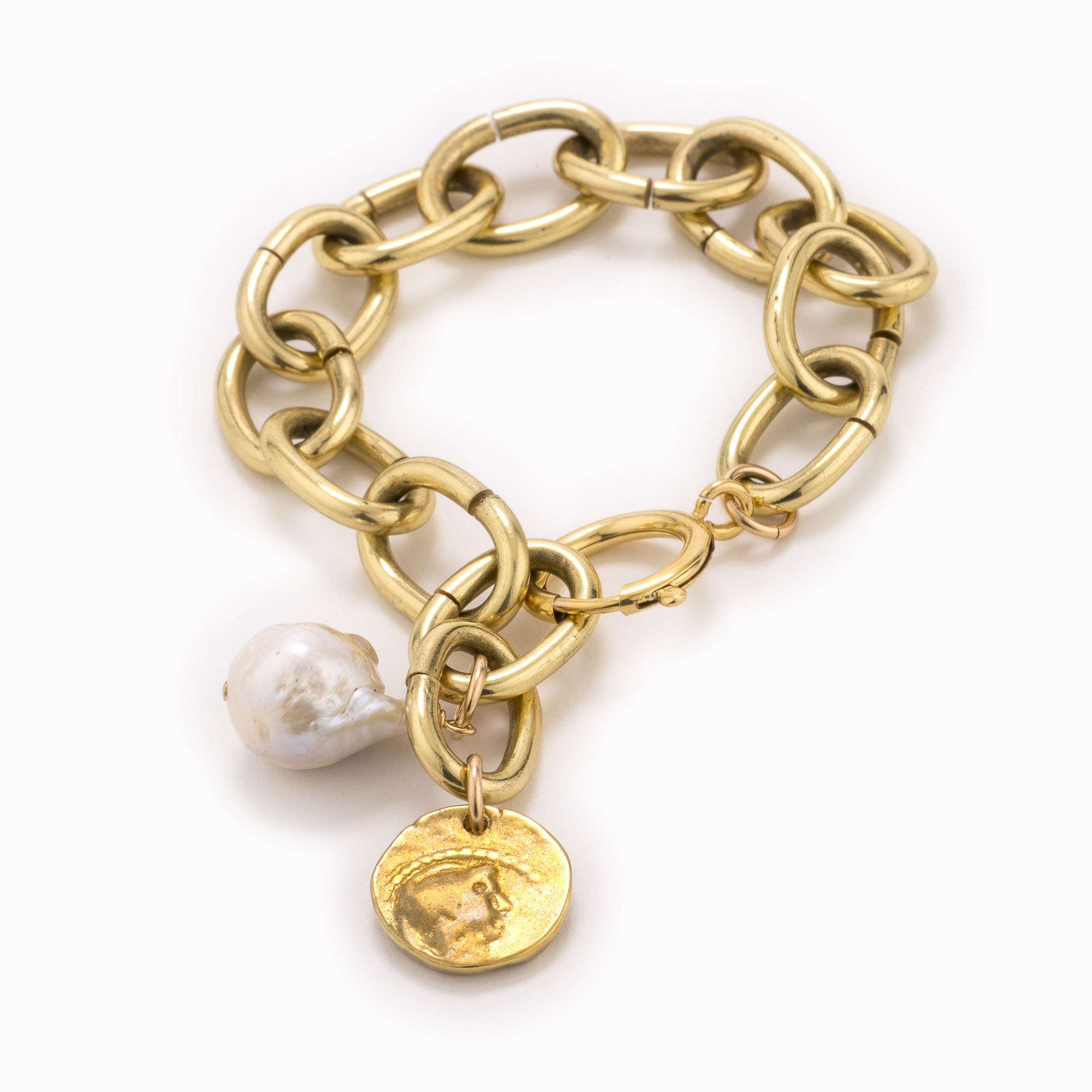 An adjustable, large brass chain bracelet with coin and white pearl.