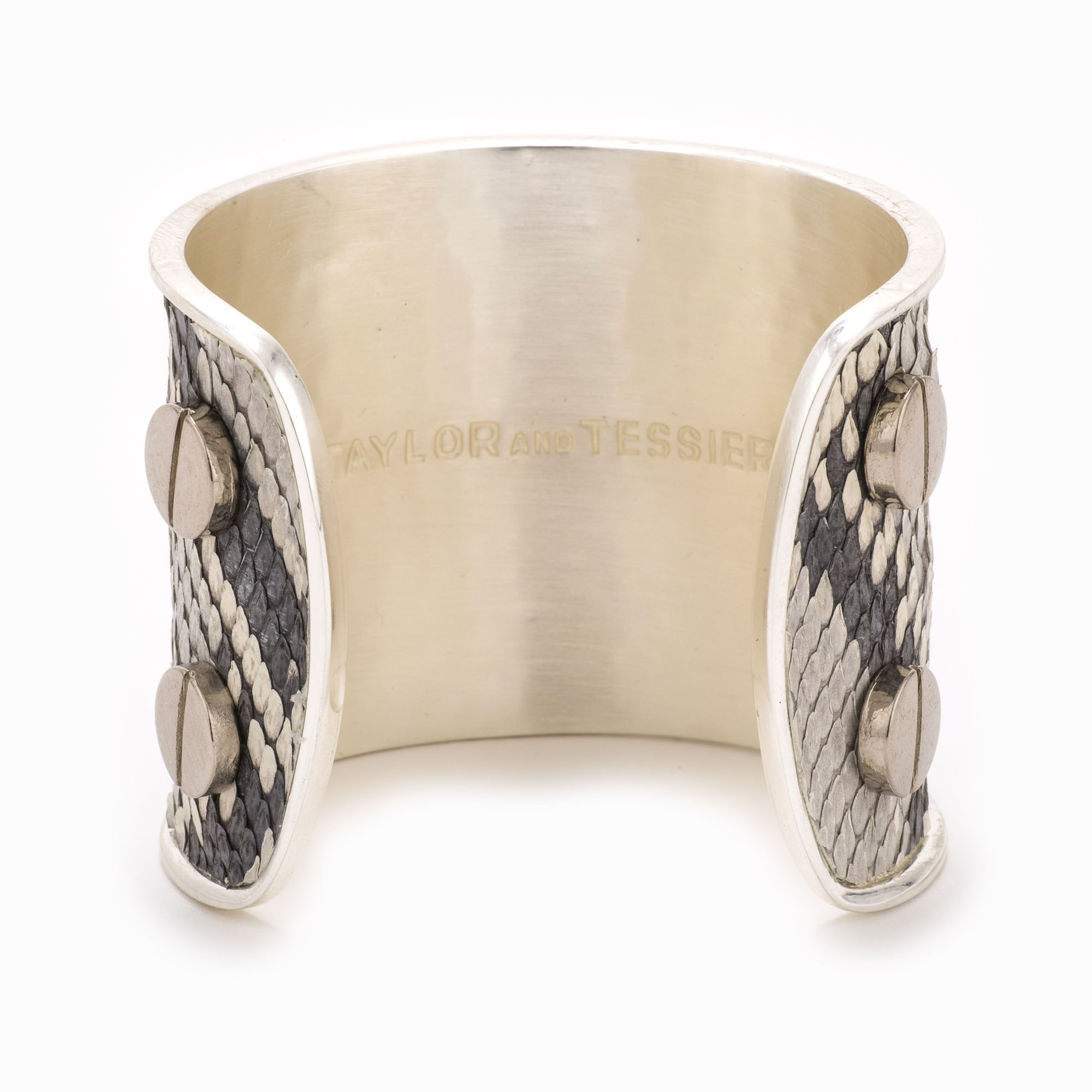 A large silver cuff with black and white colored snakeskin pattern inlaid.