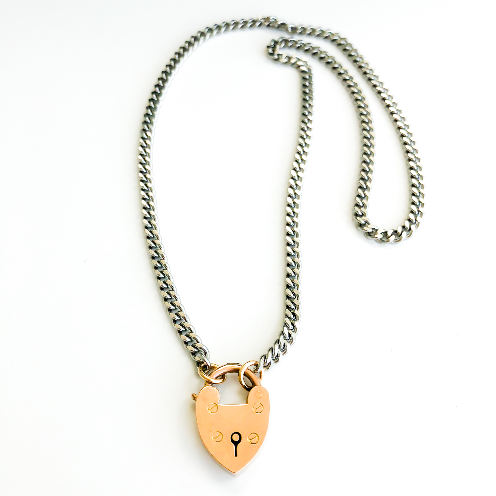 An oxidized sterling silver chain necklace laying with 9k rose gold vintage padlock.